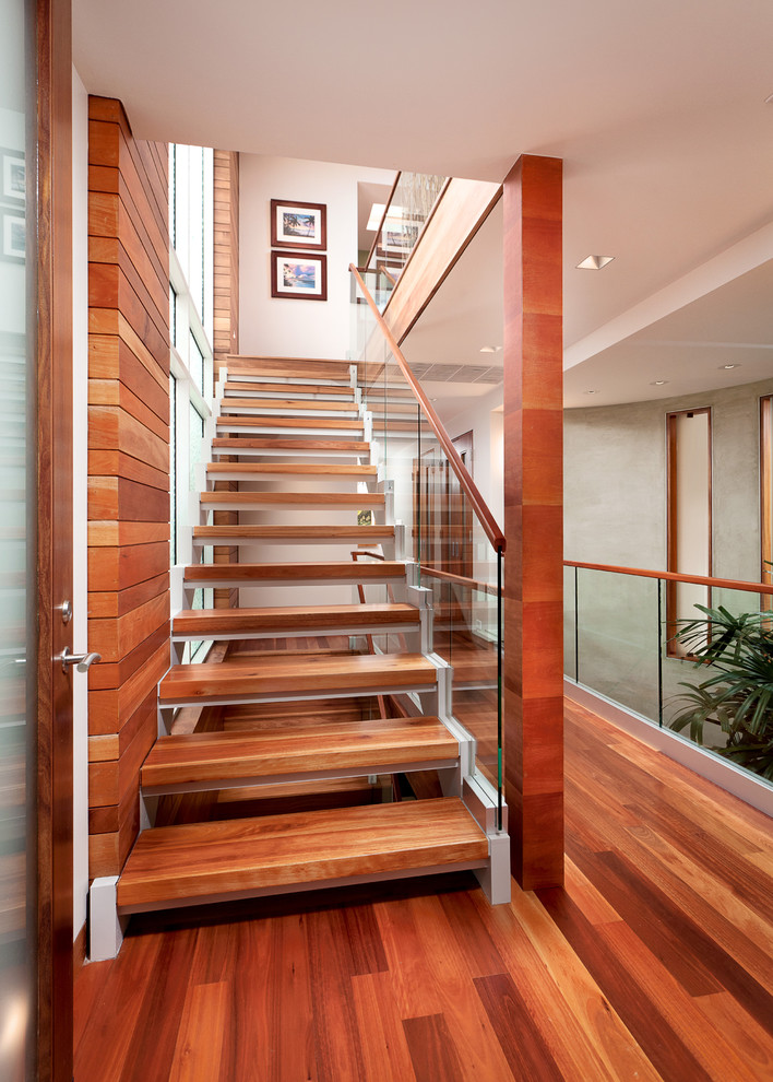 glass stair railing lyptus ward wood floor wood cap wood wall small and big glass windows framed pictures indoor plant white wall and ceiling