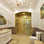 Gold Bathroom Chandelier Framed Wall Art Framed Wall Mirror Gold Accents Gold Fixtures Gold And White Tiles Glass Shower Door White Vanity
