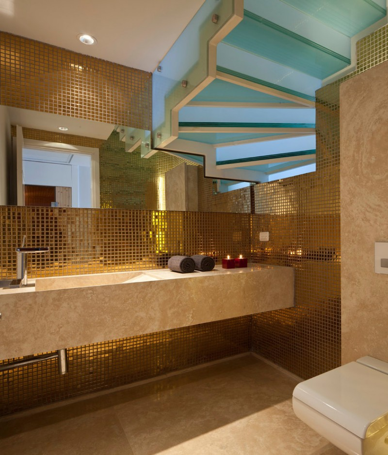 gold bathroom exposed stairs floating vanity freestanding vanity frosted glass stairs gold backsplash tile gold tile wall horizontal mirror