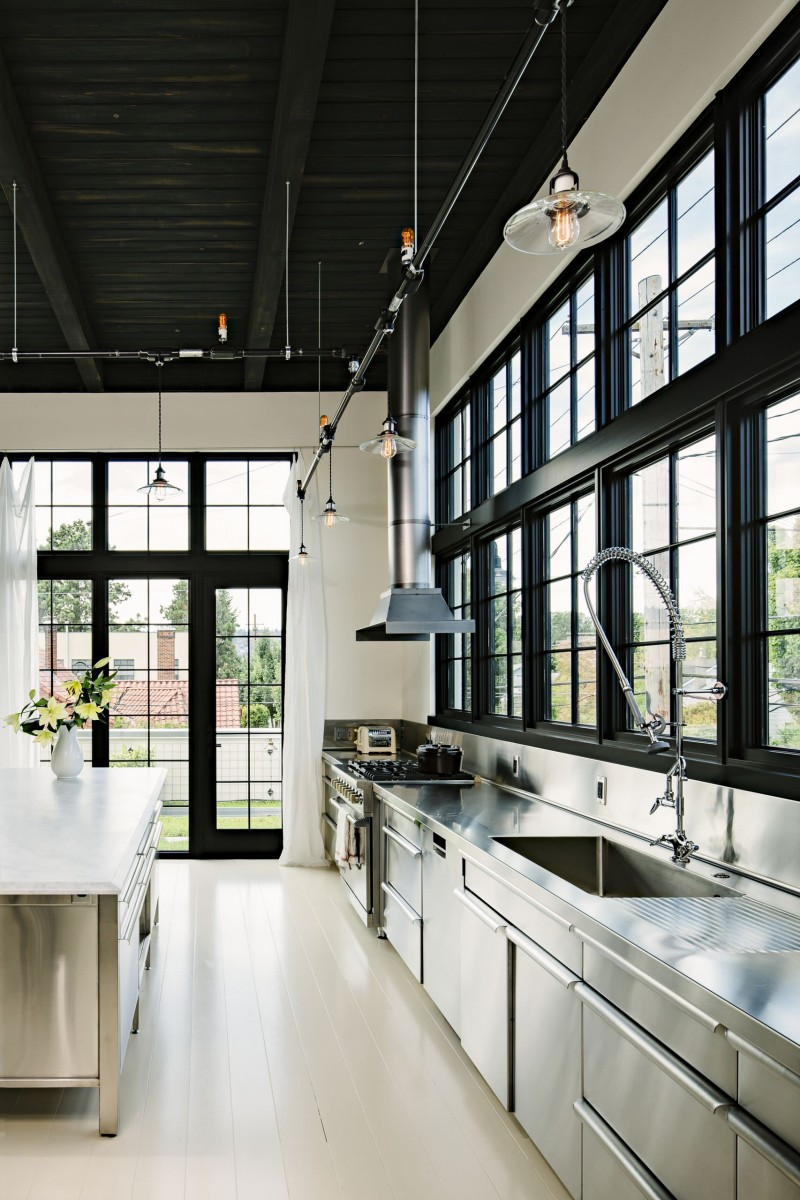 high ceiling black trim glass door track lighting stainless steel cabinet stainless steel countertop metalic backsplash metalic hood