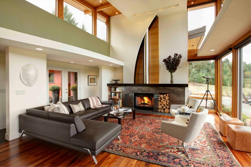high ceiling leather sectional armchair area rug wooden floor glass table wood fireplace telescope green wall oversized window built in bookcase