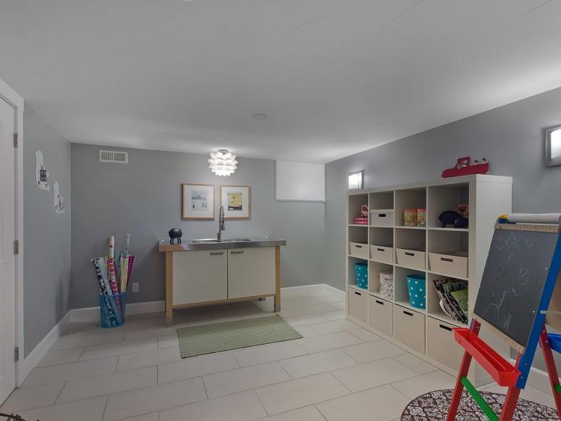 kids easel chalkboard brownstone contemporary playroom hardwood flooring purple bedding storage basket cabinet sink