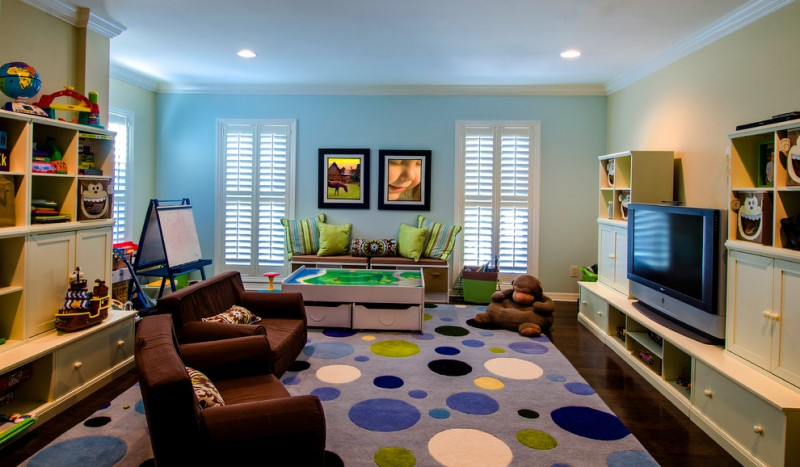 kids easel colorful dotted rug blue wall brown armchair built in cabinets dark wood floor green throw pillows big tv cabinet brown chairs