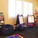 Kids Easel Two Chalkboard Easel Area Rug Small Colorful Rug Bookshelves Red Wood Chairs Floor Cushions Windows Craft Table