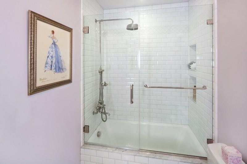 lavender bathroom tub shower glass shower doors shower faucet white wall tile built in shelves artwork