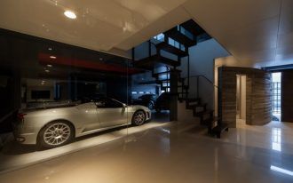 modern garage glass wall recessed lighting granite flooring cars wood stairs glass wailing white wall and ceiling accent wall