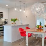 Red Chairs White Chandelier Big Mirror Wooden Table Fruits Brown Floor White Kitchen Cabinet Built In Oven Sink Kitchen Island