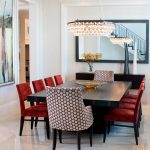 Red Chairs White Patterned Chairs Black Dining Table Pearls Chandelier Big Mirror With Black Frame Floating Cabinet Artwork