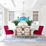 Red Chairs Wood Dining Table White Cushioned Chairs Blue And White Rug Medium Tone Floor Indoor Plants Chandelier Windows With Shades Glass Doors