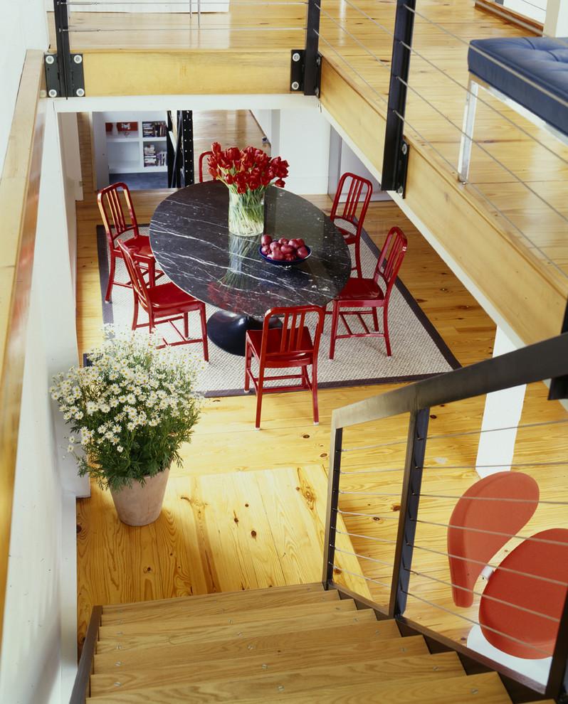 red chairs wood stairs and railings dark marble saarinen oval dining table wood floor flower arrangement indoor plants area rug