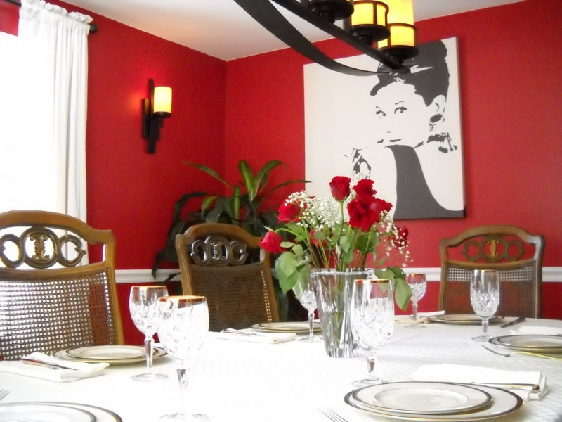 red dining room black and white artwork wall sconce indoor plant dining table and chairs chandelier white curtain black curtain rod