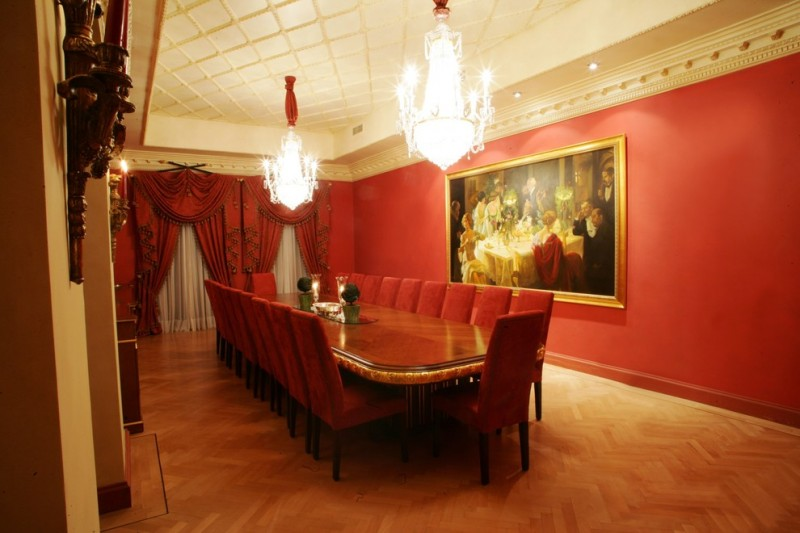 red dining room chandeliers red dining table and chairs red walls artwork wood flooring red curtains herringbone floor
