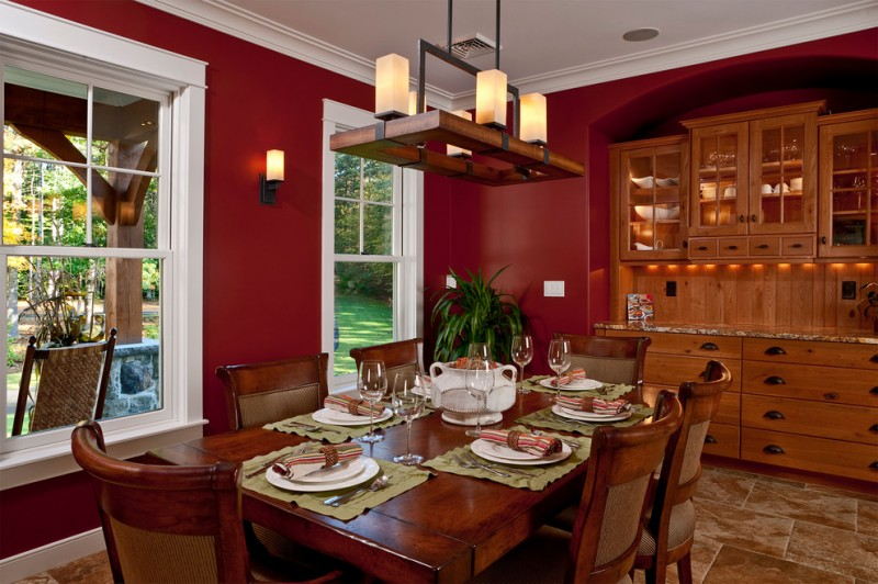 red dining room glass windows with white frame chandelier brown cabinet and drawers brown tile floor wood table and chairs