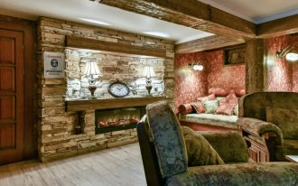 red wall accent wall red pillow accent couch stone wall stone fireplace wooden floor wood door exposed beams wall lamps