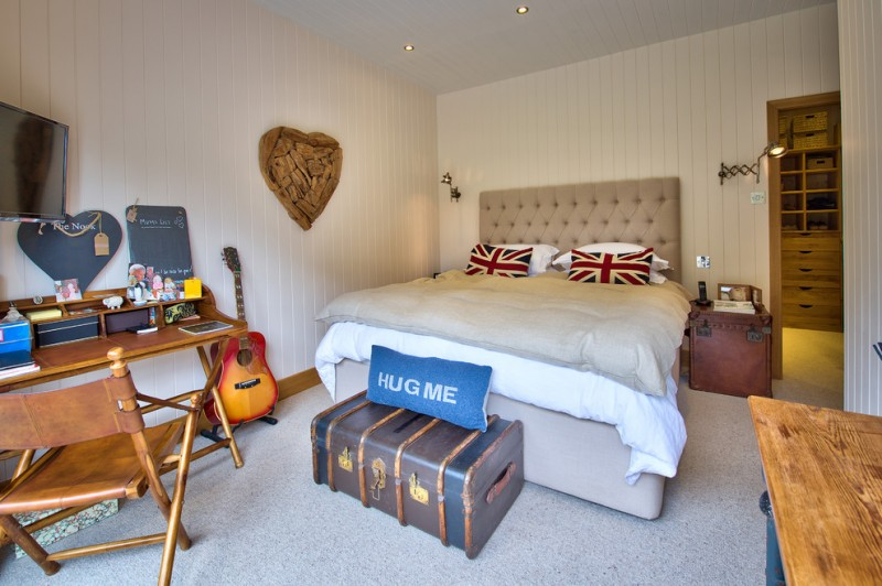 retro bedroom beige tufted bed driftwood guitar panelled walls recessed lights wood nightstands wall sconces grey rug