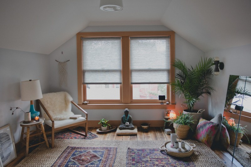 sloped ceiling attic wooden floor area rug window covering wall lamp plant armchair side table ceiling lamp