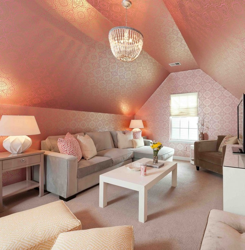 sloped ceiling pink wallpaper chandelier grey sectional window with shade table lamp side table floor cushions brown armchair
