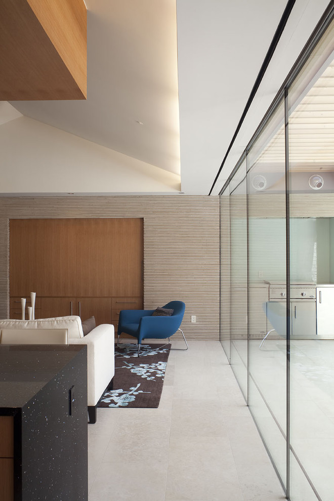 sloped ceiling recessed lighting blue armchair glass window and wall glass door large area rug black cabinet white couch