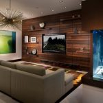 Wooden Wall Shelves Accent Wall Area Rug Concrete Floor Large Aquarium Long Sofa Lumiere Chandelier Media Wall Recessed Lighting Wood Wall