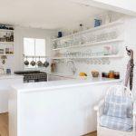 Wooden Wall Shelves Bookshelves Glassses Shelves White Kitchen White Armchair Blue Cushion Medium Tone Wood Floor Minimalist Kitchen Cabinet