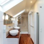 Bamboo Bathroom Flat Panel Cabinets White Cabinets Beige Walls A Vessel Sink Wood Countertops Sloped Ceiling With Glasses Wall Sconces