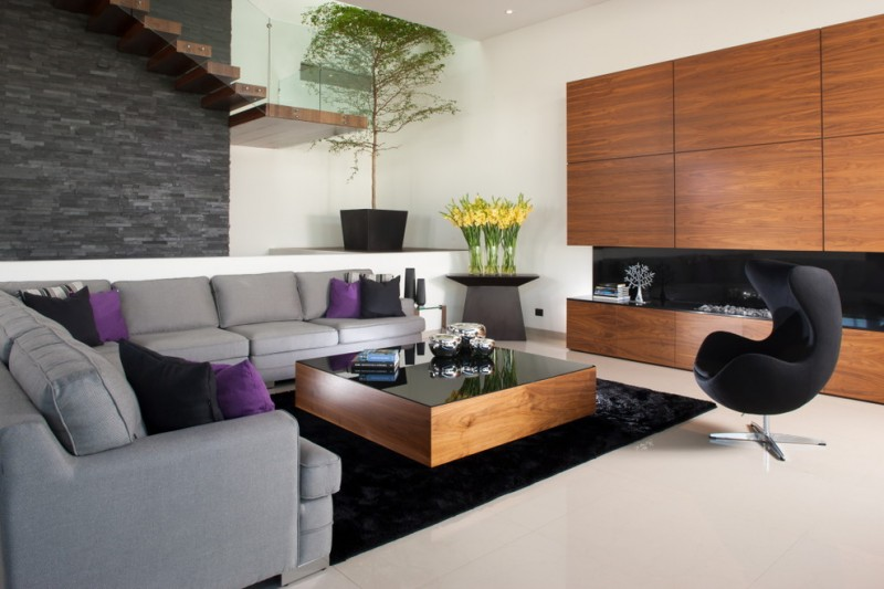 black rugs for living room black gloss coffee table black egg chair grey sofa stone wall pillows glass railing indoor plants