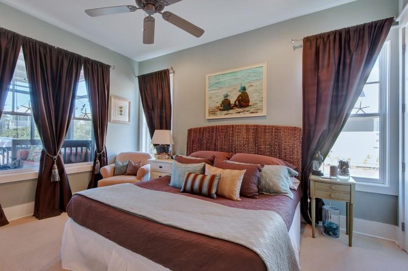 curtain tassels dark brown curtains headboard beige armchair windows ceiling fan artwork brown bedding nightstands table lamp