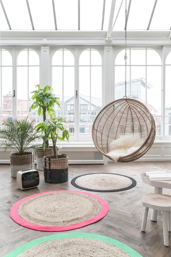 hanging papasan chairs colorful round rustic rug indoor plants glass windows and ceiling shag chair cushion wood flooring