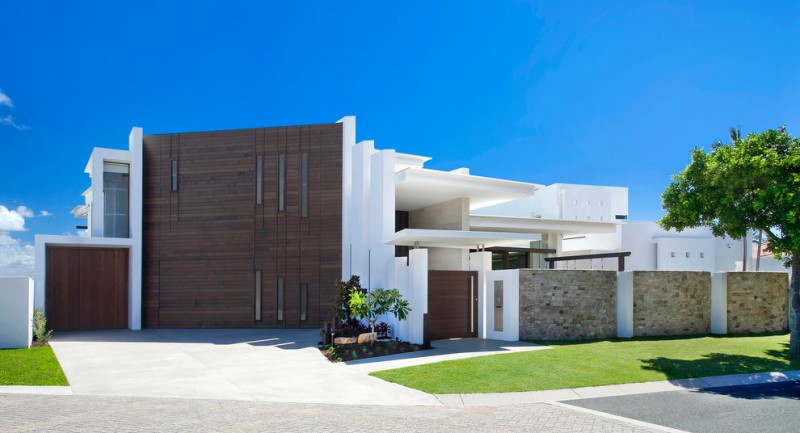 modern mansion exterior flat roof design wood accent high wall frosted glass windows stone wall grass yard small garden