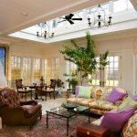 Open Ceiling Rustic Chandeliers Black Ceiling Fan Colorful Sofas And Pillows Brown Leathered Armchair Indoor Plant Windows Artwork