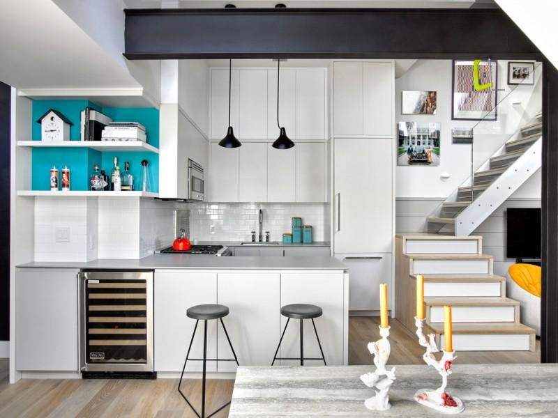 peninsular kitchen drop in sink flat panel grey cabinets white backsplash stainless steel appliances barstools black pendants