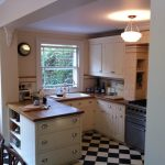 Peninsular Kitchen Shelves Drawers Wood Countertop Window Black And White Floor Tile Chandelier Stove Undermount Sink White Glass Door