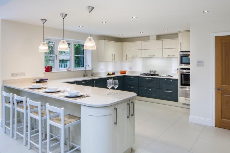 peninsular kitchen white pendants white countertop windows recessed lightings white barstools undermount sink storages