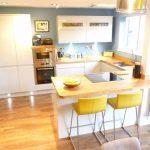 Peninsular Kitchen Yellow Barstools White Kitchen Cabinet Wood Countertop Blue Wall Window Recessed Lighting Undermount Sink