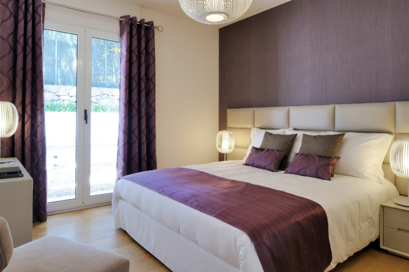 purple accent walls white bedding purple throw and pillows grey headboard chandelier nightstands glass doors purple curtains
