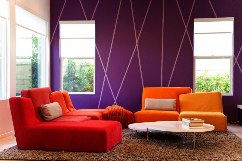 purple accent walls white wall windows orange and red couches brown fluffy rug white coffee table 2 in 1 beige pillow