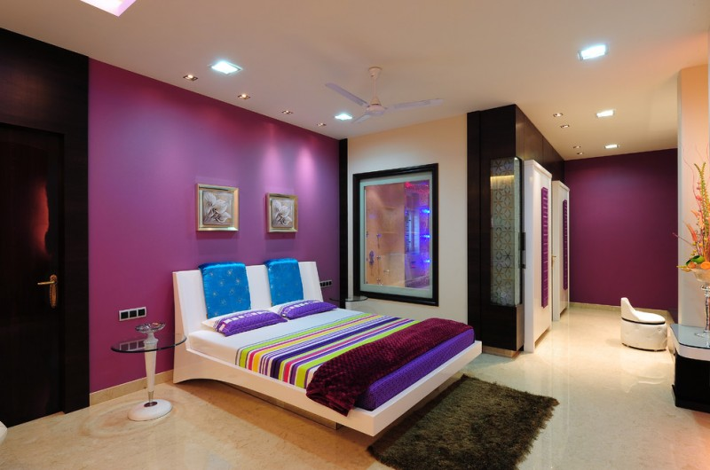 purple master bedroom white bed with headboard purple walls colorful bedding ceiling fan recessed lighting glass round table brown shag rug