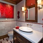 Red Bathroom Accessories Red Artwork Red And Beige Floor Tiles Wood Vanity White Countertop And Sink Mirror Wall Sconces