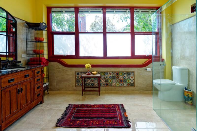 red bathroom accessories red frame windows red mediterranean rug black rack red bowls glass shower doors wood vanity black countertop