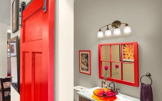 red bathroom accessories red sliding barn door red frame mirror marble countertop wood cabinet towel ring wall pendant wood floor