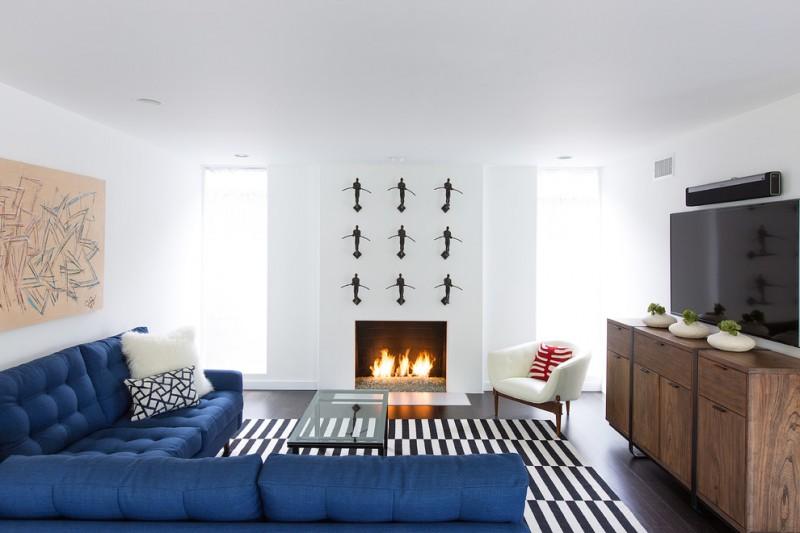 royal blue sofa artwork black and white rug glass coffee table windows fireplace art wall decor wood cabinet dark floor