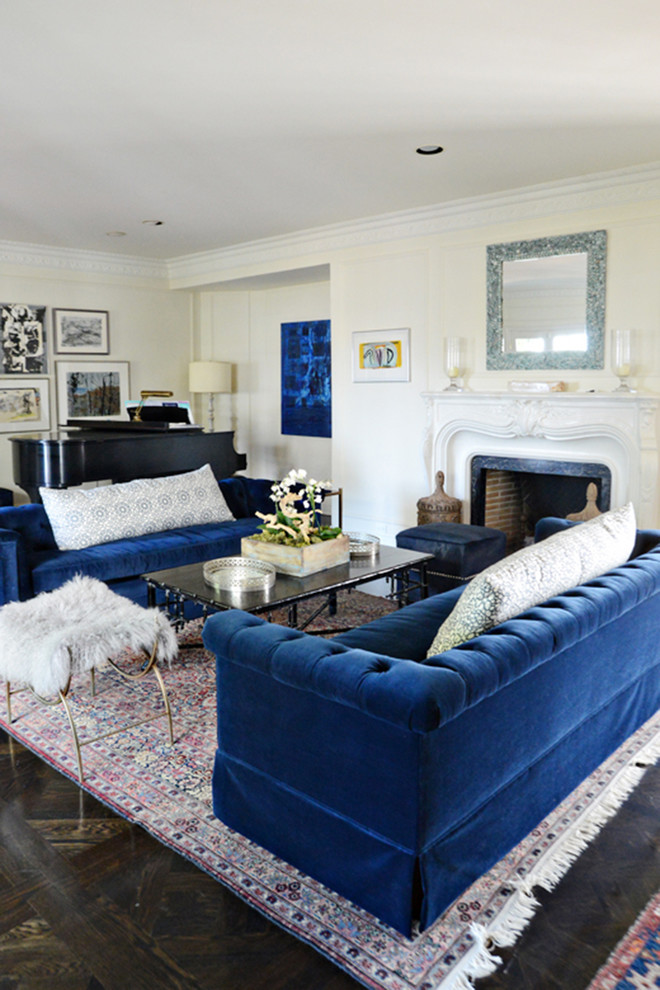 royal blue sofa glass coffee table area rug white shag chair mirror fireplace dark flooring artworks floor lamp fireplace mantel dark blue ottoman