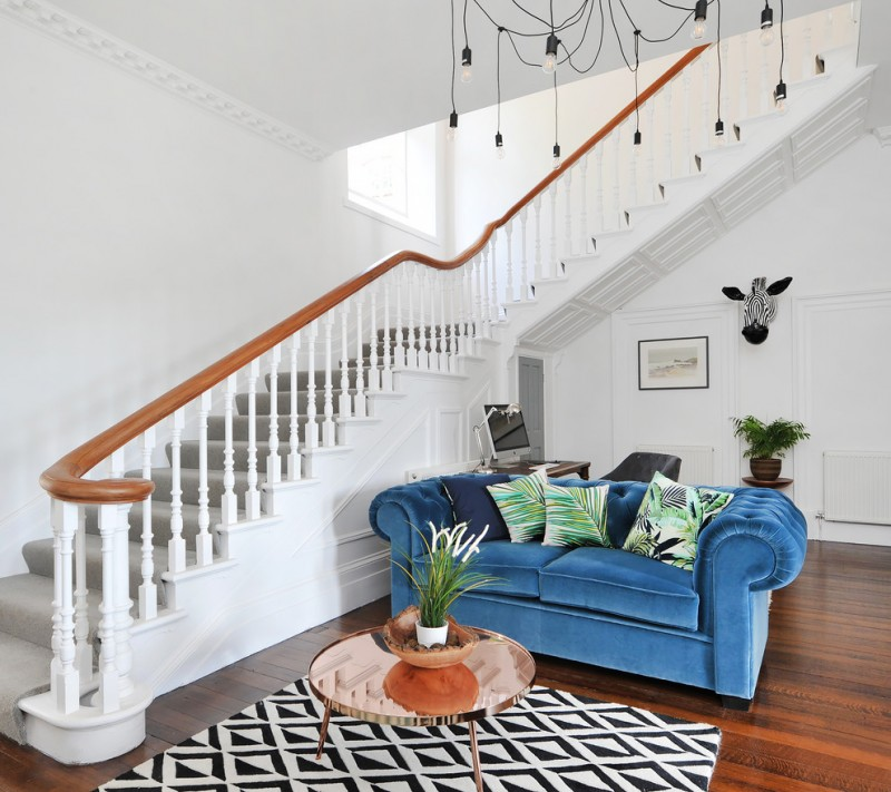 royal blue sofa unique lighting fixture staircase with wood railing black and white rug small round table wood flooring indoor plant