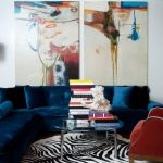 Royal Blue Sofa White Chandelier Colorful Artworks Cow Hide Rug Glass Table Wood Flooring Blue Pillows Red Armchair