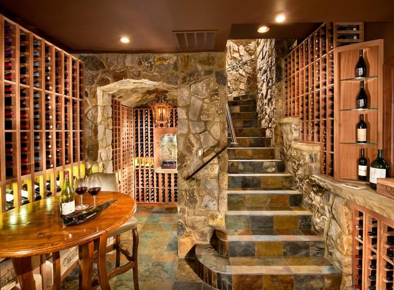 stone staircase stone wall slate floor wooden racks rounded table bar stool open shelving