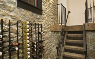 stone wall chrome wine racks staircase railing brick floor black trim window