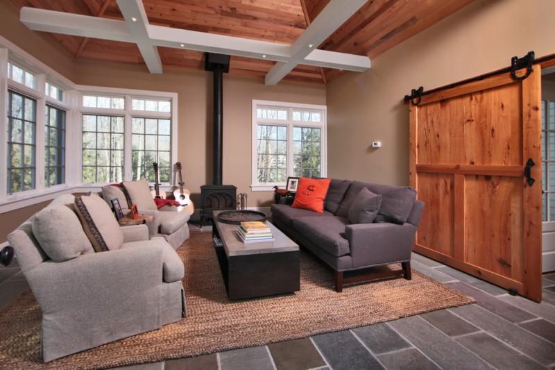 tan living room grey couch grey armchairs coffee table area rug tan walls open ceiling big barn door grey floor tiles windows