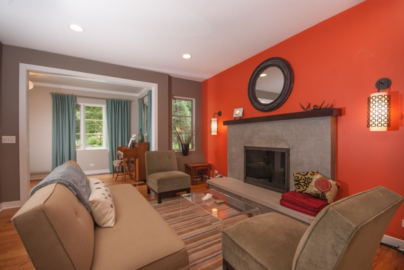 tan living room orange accent wall round mirror tan couch and chairs glass coffee table colorful striped rug fireplace wall sconces
