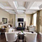 Tan Living Room Stone Fireplace Wall Wood Floor Ceiling Style Black Framed Mirror Tan Curtains Tan Sofa White Armchair Ottoman
