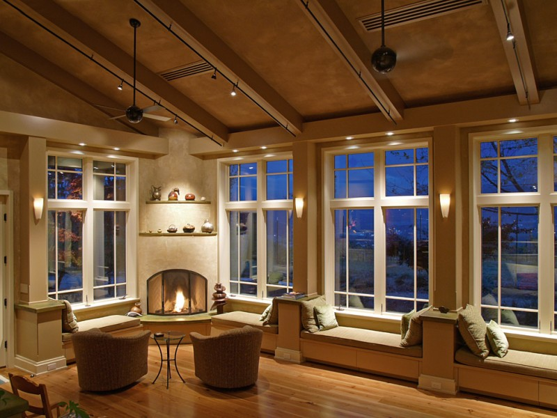 tan living room tan ceiling light wood floor window benches tan armchairs small coffee table corner fireplace ceiling fans wall sconces